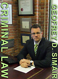 Geofrey Simair, Criminal Defense Lawyer at his desk near Downtown Bay Centre in Victoria, BC